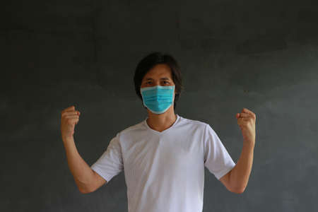 Man wearing hygienic mask and wearing white shirt and standing with raised both fist on dark wall background. Concept of protect tiny dust or disease.