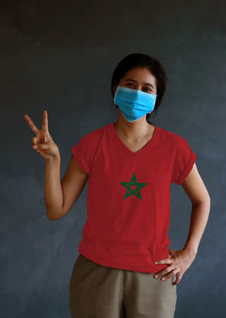Woman wearing hygienic mask and wearing Moroccan flag colored shirt and raising two fingers up on dark wall background. Concept of protect tiny dust or disease of Morocco.
