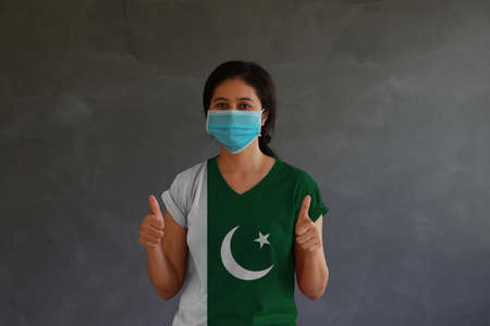 Masked woman wearing Pakistan flag color of shirt and thumbs up with both hands on dark wall background. Concept of protection and fighting COVID.