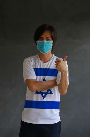 Man wearing hygienic mask and wearing Israeli flag colored shirt and cross one s arm with thumbs up on dark wall background. Concept of protect tiny dust or disease of Israel. Archivio Fotografico - 157263843