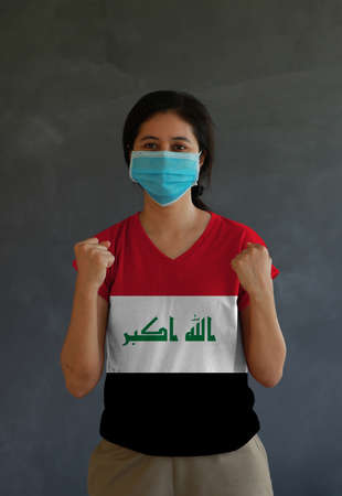 Woman wearing hygienic mask and wearing Iraq flag colored shirt and standing with raised both fist on dark wall background. Concept of protect tiny dust or disease. Archivio Fotografico - 157263844