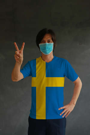 Man wearing hygienic mask and wearing Swedish flag colored shirt and raising two fingers up on dark wall background. Concept of protect tiny dust or disease of Sweden.