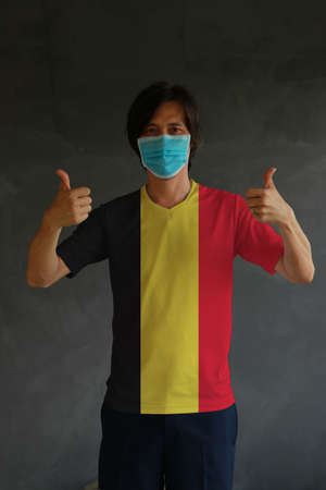 Man wearing hygienic mask and wearing Belgian flag colored shirt with thumbs up on both hands. Concept of protect tiny dust or disease of Belgium.