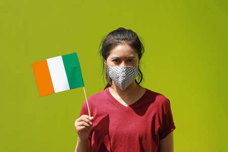 Masked woman in brown shirt and Ivory Coast flag in hand. Concept of protection and fighting COVID.