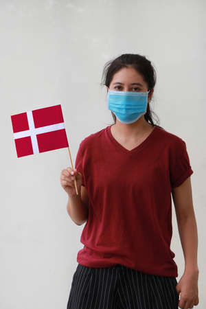Masked woman in brown shirt and Denmark flag in hand. Concept of protection and fighting COVID. Archivio Fotografico - 157263848