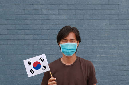 Masked man in brown shirt and South Korea flag in hand. Concept of protection and fighting COVID 19.