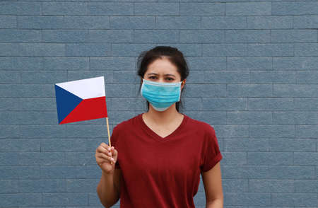 Masked woman in brown shirt and Czech Republic flag in hand. Concept of protection and fighting COVID. Archivio Fotografico