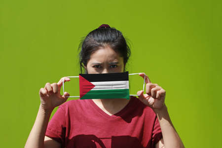 A woman and hygienic mask with Palestine flag pattern in her hand and raises it to cover her face on green background. A mask is a very good protection from Tiny Particle or virus corona. Archivio Fotografico - 157263851