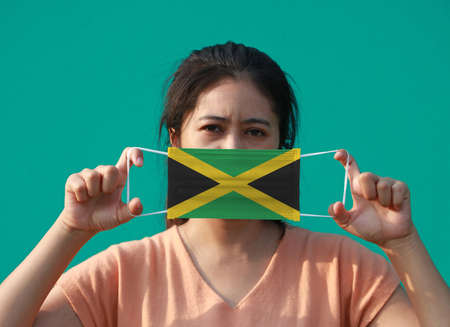 A woman with Jamaica flag on hygienic mask in her hand and lifted up the front face on green background. Tiny Particle or virus corona or Covid 19 protection. Concept of Combating illness. Archivio Fotografico - 157847180