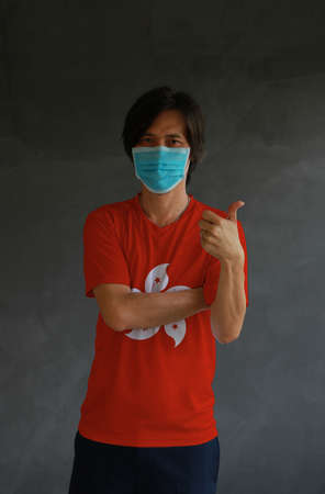 Man wearing hygienic mask and wearing Hong Kong flag colored shirt and cross one s arm with thumbs up on dark wall background. Concept of protect tiny dust or disease.