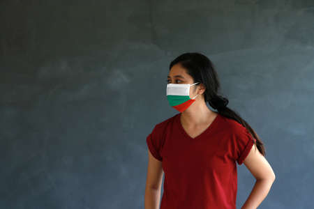 Woman wearing Bulgarian flag colored hygienic mask with brown shirt and facing to the side on dark wall background. Concept of protect tiny dust or disease of Bulgaria.
