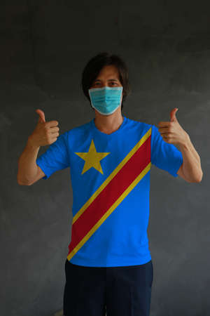Man wearing hygienic mask and wearing DR Congo flag colored shirt with thumbs up on both hands. Concept of protect tiny dust or disease of Democratic Republic of the Congo. Archivio Fotografico - 157847187