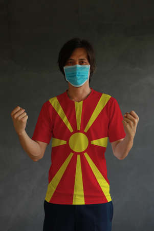 Man wearing hygienic mask and wearing North Macedonia flag colored shirt and standing with raised both fist on dark wall background. Concept of protect tiny dust or disease. Archivio Fotografico - 157847191