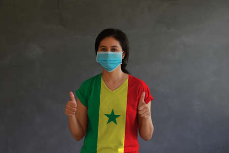 Woman wearing hygienic mask and wearing Senegal flag colored shirt with thumbs up with both hands on dark wall background. Concept of protect tiny dust or disease.