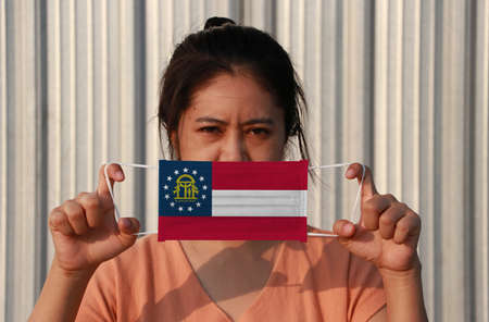 A woman and hygienic mask with Georgia flag pattern in her hand and raises it to cover her face on grey background. A mask is a very good protection from Tiny Particle or virus corona or Covid 19. Reklamní fotografie