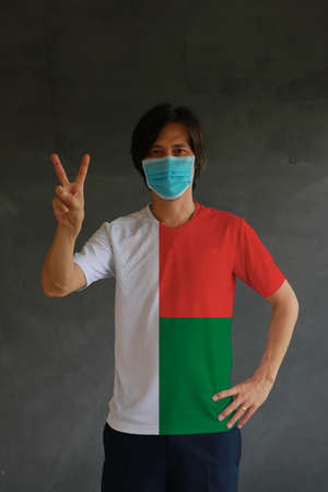 Man wearing hygienic mask and wearing Madagascar flag colored shirt and raising two fingers up on dark wall background. Concept of protect tiny dust or disease. Archivio Fotografico - 157847196