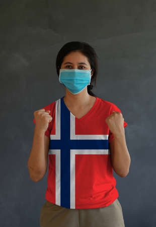 Woman wearing hygienic mask and wearing Norwegian flag colored shirt and standing with raised both fist on dark wall background. Concept of protect tiny dust or disease of Norway. Archivio Fotografico - 157847197