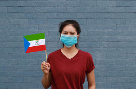 Masked woman in brown shirt and Equatorial Guinea flag in hand. Concept of protection and fighting COVID 19.