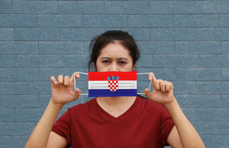A woman and hygienic mask with Croatia flag pattern in her hand and raises it to cover her face on blue wall background. A mask is a very good protection from Tiny Particle or virus corona. Archivio Fotografico - 157679351