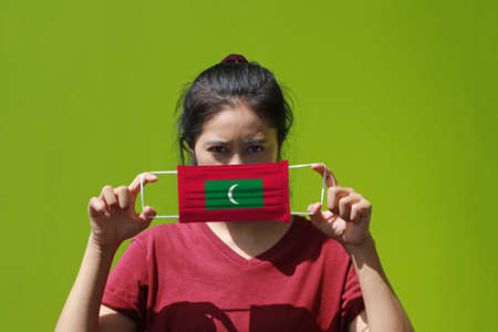 A woman and hygienic mask with Maldives flag pattern in her hand and raises it to cover her face on green background. A mask is a very good protection from Tiny Particle or virus corona. Reklamní fotografie