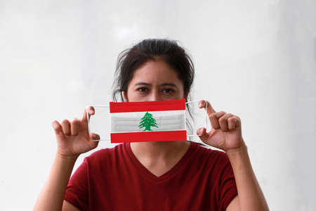 A woman and hygienic mask with Lebanon flag pattern in her hand and raises it to cover her face on white background. A mask is a very good protection from Tiny Particle or virus corona. Archivio Fotografico - 157679353
