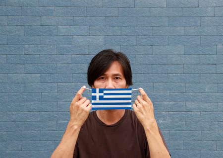 A man and hygienic mask with Greece flag pattern in his hand and raises it to cover his face on blue wall background. A mask is a very good protection from Tiny Particle or virus corona.