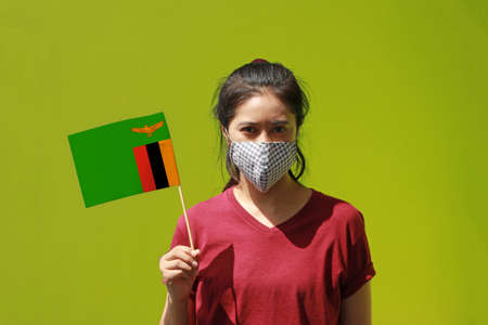 Masked woman in brown shirt and Zambia flag in hand. Concept of protection and fighting COVID 19. Archivio Fotografico