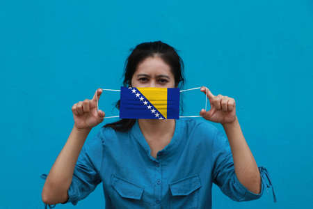 A woman and hygienic mask with Bosnia and Herzegovina flag pattern in her hand and raises it to cover her face on blue background. A mask is a very good protection from Tiny Particle or virus corona. Archivio Fotografico
