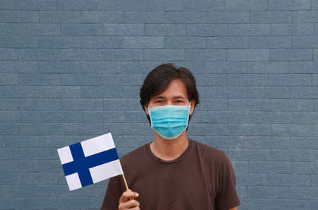 Masked man in brown shirt and Finland flag in hand. Concept of protection and fighting COVID 19.