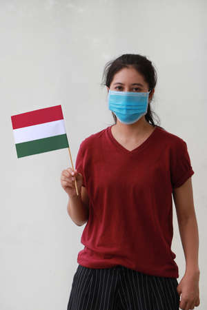 Masked woman in brown shirt and Hungary flag in hand. Concept of protection and fighting COVID 19.