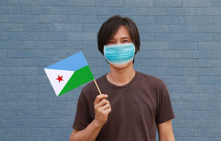 Masked man in brown shirt and Djibouti flag in hand. Concept of protection and fighting COVID 19. Archivio Fotografico - 157679359