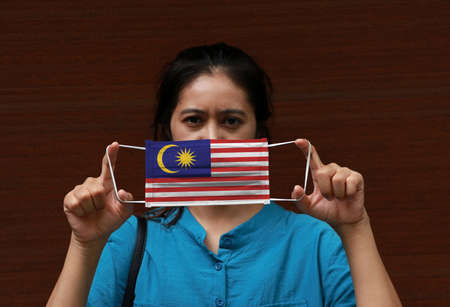 A woman and hygienic mask with Malaysia flag pattern in her hand and raises it to cover her face on dark background. A mask is a very good protection from Tiny Particle or virus corona.