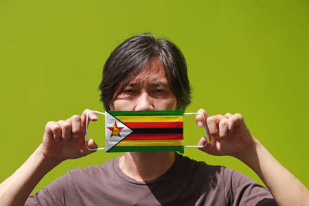 A man and hygienic mask with Zimbabwe flag pattern in his hand Archivio Fotografico