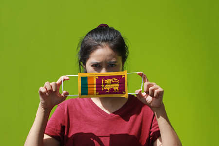 A woman and hygienic mask with Sri Lanka flag pattern in her hand