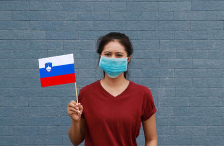 Masked woman in brown shirt and Slovenia flag in hand. Archivio Fotografico