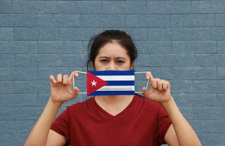 A woman and hygienic mask with Cuba flag pattern in her hand