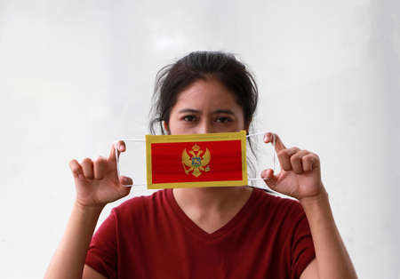 A woman and hygienic mask with Montenegro flag pattern in her hand Archivio Fotografico - 157877453