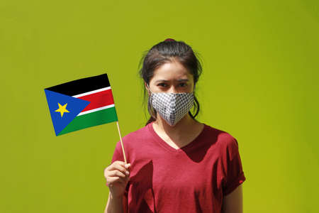 Masked woman in brown shirt and South Sudan flag in hand.