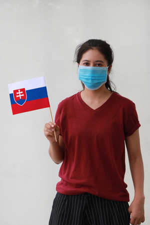Masked woman in brown shirt and Slovakia flag in hand. Archivio Fotografico - 157877457