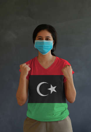 Woman wearing hygienic mask and wearing Libya flag colored shirt and standing with raised both fist on dark wall background. Concept of protect tiny dust or disease.