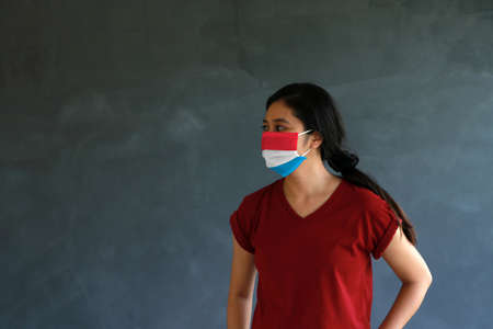 Woman wearing Luxembourg flag colored hygienic mask with brown shirt and facing to the side on dark wall background. Concept of protect tiny dust or disease.