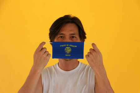 A man and hygienic mask with Oregon flag pattern in his hand and raises it to cover his face on yellow background. A mask is a very good protection from Tiny Particle or virus corona or Covid 19. Archivio Fotografico - 158025132