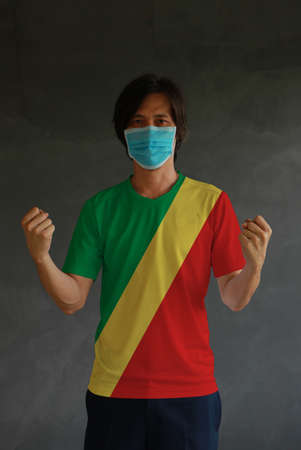 Man wearing hygienic mask and wearing Congo flag colored shirt and standing with raised both fist on dark wall background. Concept of protect tiny dust or disease. Archivio Fotografico