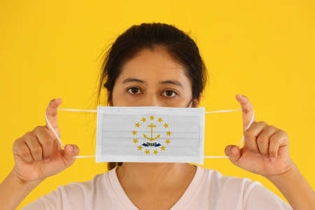 A woman and hygienic mask with Rhode Island flag pattern in her hand and raises it to cover her face on yellow background. A mask is a very good protection from Tiny Particle or virus corona or Covid 19. Archivio Fotografico
