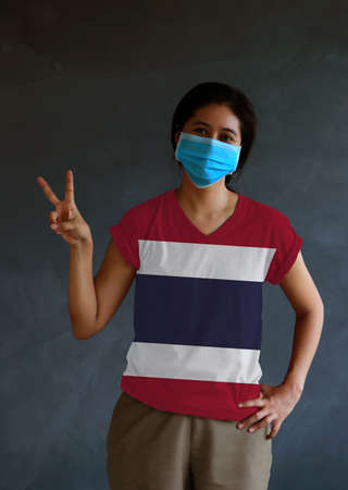 Woman wearing hygienic mask and wearing Thai flag colored shirt and raising two fingers up on dark wall background. Concept of protect tiny dust or disease of Thailand.