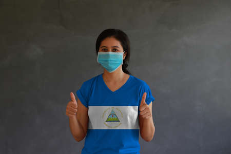 Woman wearing hygienic mask and wearing Nicaragua flag colored shirt with thumbs up with both hands on dark wall background. Concept of protect tiny dust or disease.