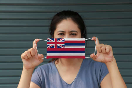 A woman and hygienic mask with Hawaii flag pattern in her hand and raises it to cover her face. A mask is a very good protection from Tiny Particle or virus corona or Covid 19.