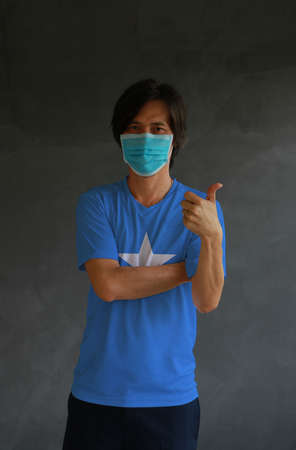 Man wearing hygienic mask and wearing Somalia flag colored shirt and cross one s arm with thumbs up on dark wall background. Concept of protect tiny dust or disease.
