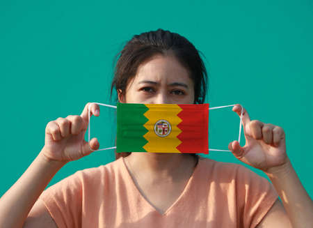 A woman and hygienic mask with los angeles flag pattern in her hand and raises it to cover her face. A mask is a very good protection from Tiny Particle or virus corona or Covid 19. Archivio Fotografico