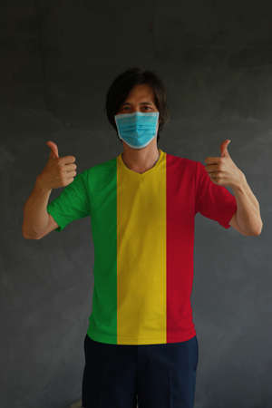 Man wearing hygienic mask and wearing Mali flag colored shirt with thumbs up on both hands. Concept of protect tiny dust or disease. Archivio Fotografico - 158025163